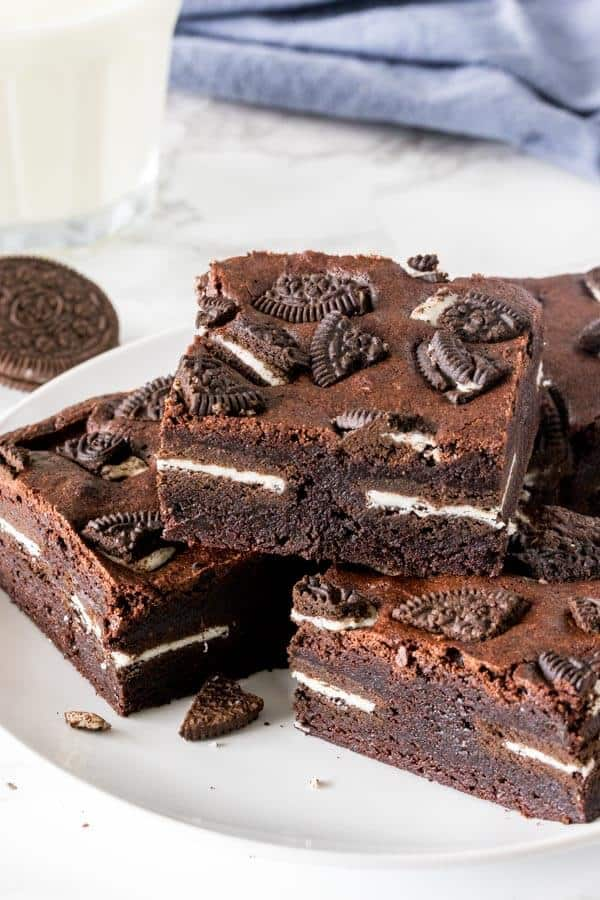 A plate of thick, fudgy Oreo brownies that are stuffed with Oreos and have crushed Oreos on top.
