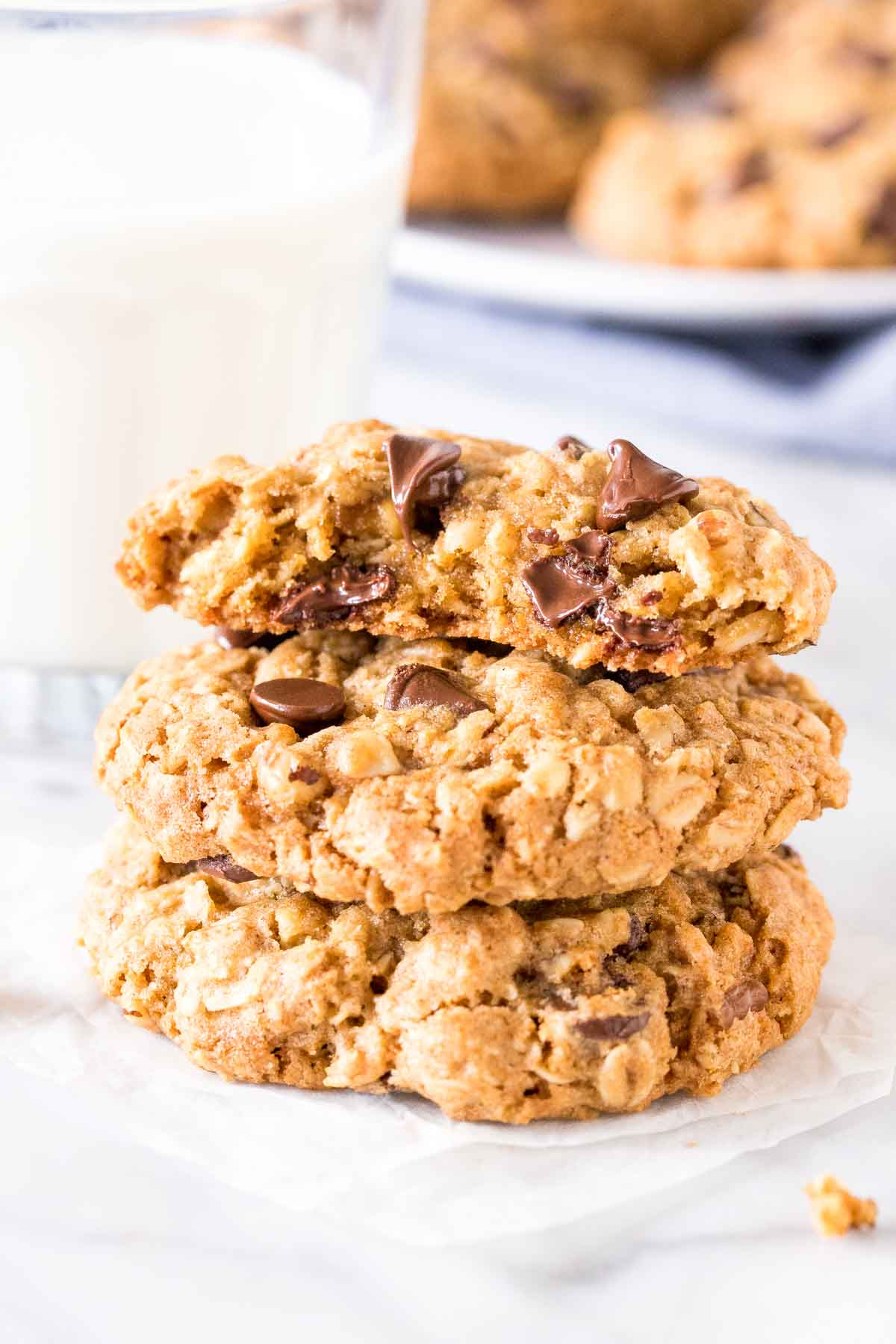 Stack of 3 oatmeal chocolate chip cookies with the top cookie broken in half.