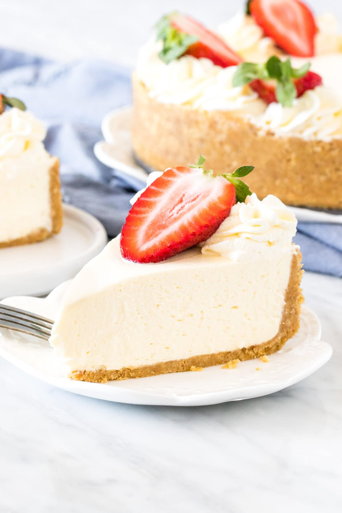 Slice of no bake cheesecake with crunchy graham crumb crust on a plate.