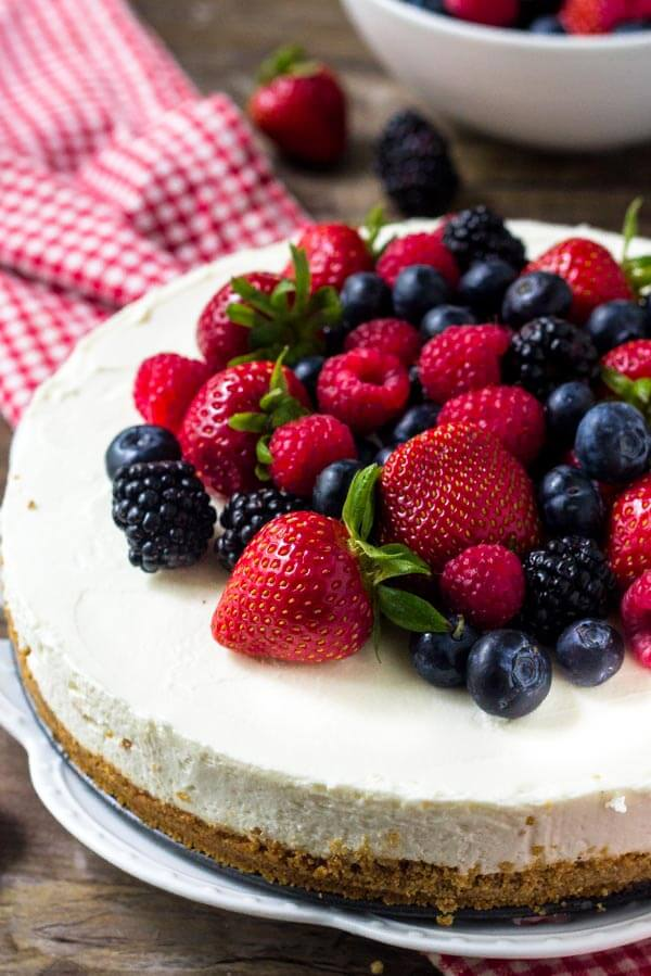 Easy no bake cheesecake with a graham cracker crust, creamy cheesecake filling, and topped with fresh berries.