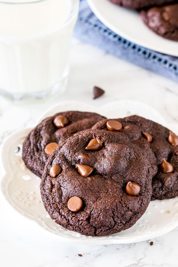 A plate of 3 double chocolate cookies with a glass of milk