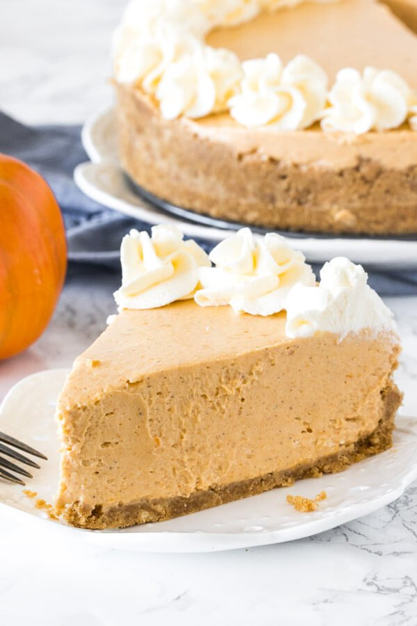 A slice of creamy no bake pumpkin cheesecake topped with whipped cream.