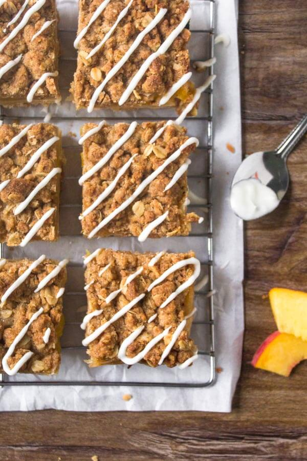 Peach Crumble Bars are filled with juicy peaches & have a buttery crumble topping & sweet glaze.