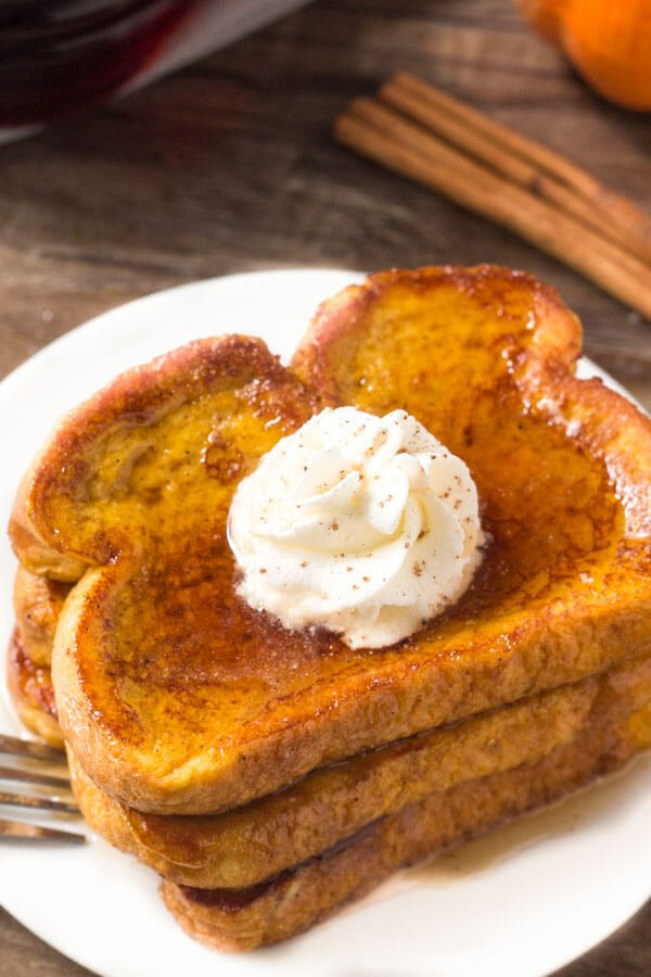 A stack of pumpkin spice french toast drizzled with maple syrup & topped with whipped cream.