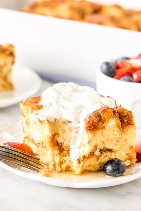 Square slice of french toast casserole with whipped cream on top and a bite taken out of it.