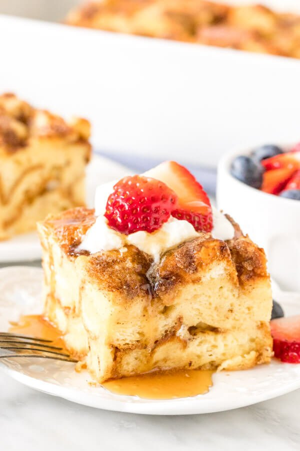 Slice of French toast casserole on a plate, topped with cream, berries and syrup.