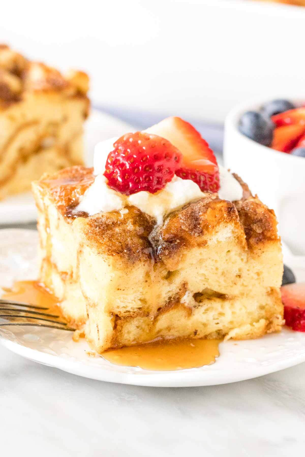 Slice of french toast bake with whipped cream, strawberries and maple syrup on top on a plate.