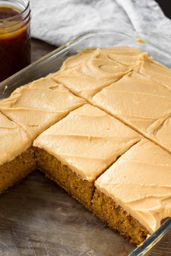 A pan of flavorful pumpkin cake with caramel cream cheese frosting.