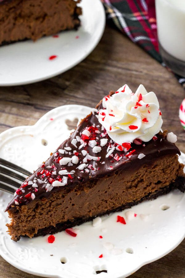 A slice of chocolate candy cane cheesecake with chocolate topping and crushed candy canes on top.