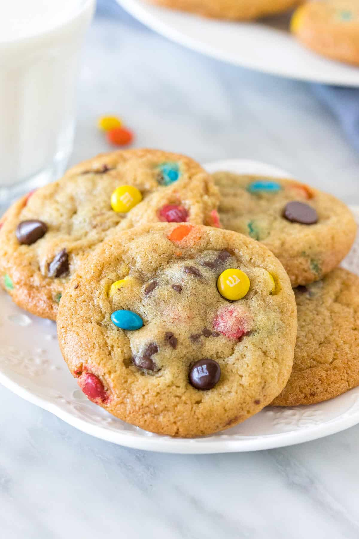 Small plate of M&M Cookies with a glass of milk