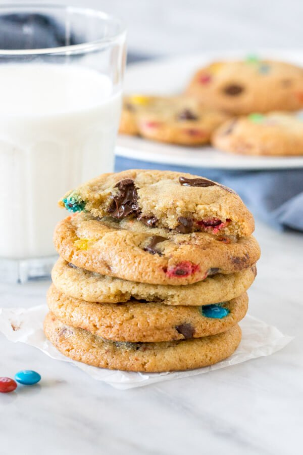 Stack of cookies with a glass of milk and plate of cookies in the background.