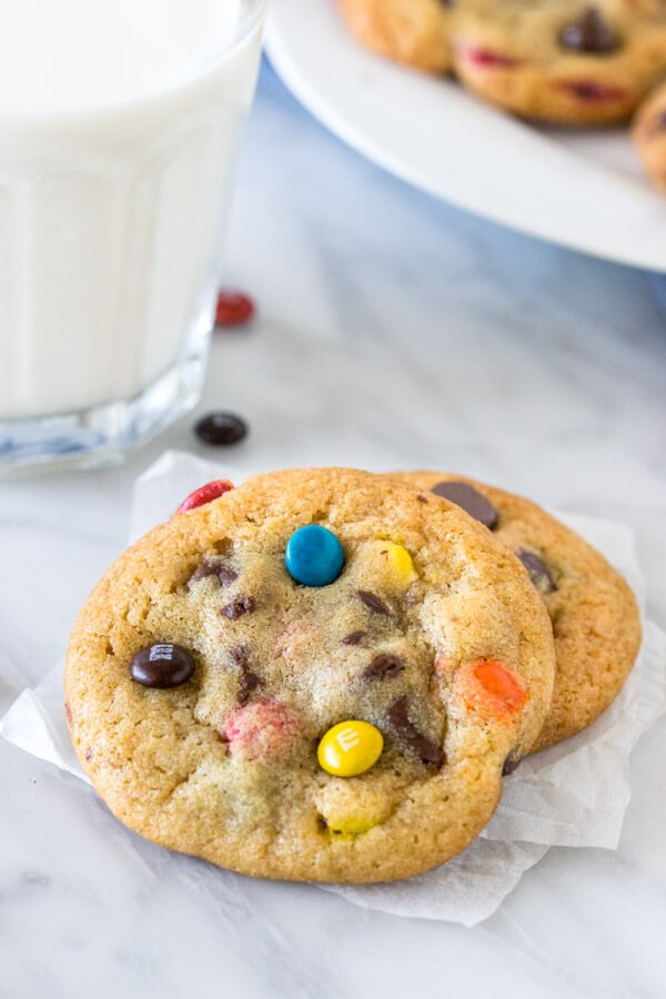 2 M&M chocolate chip cookies with a glass of milk.