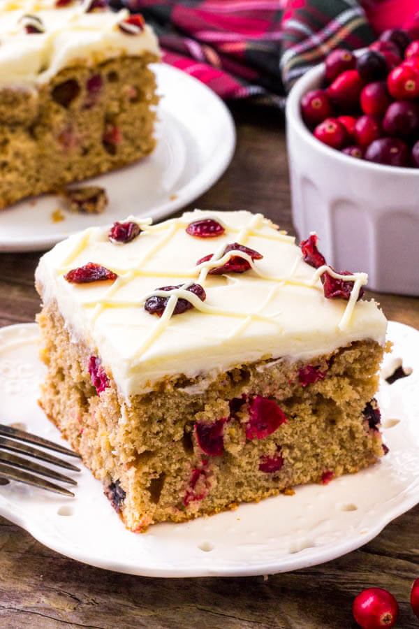 Cranberry Christmas Cake is the perfect holiday dessert. It's extra moist and super flavorful thanks to brown sugar, cinnamon, a hint of orange zest, and fresh cranberries. Topped with white chocolate cream cheese frosting.