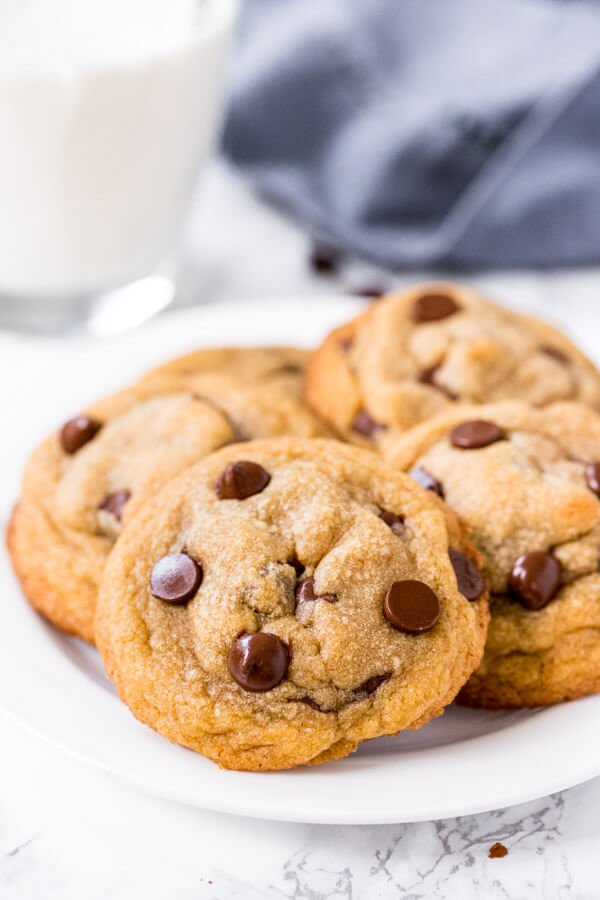 Small batch chocolate chip cookies on a white plate with a glass of milk.