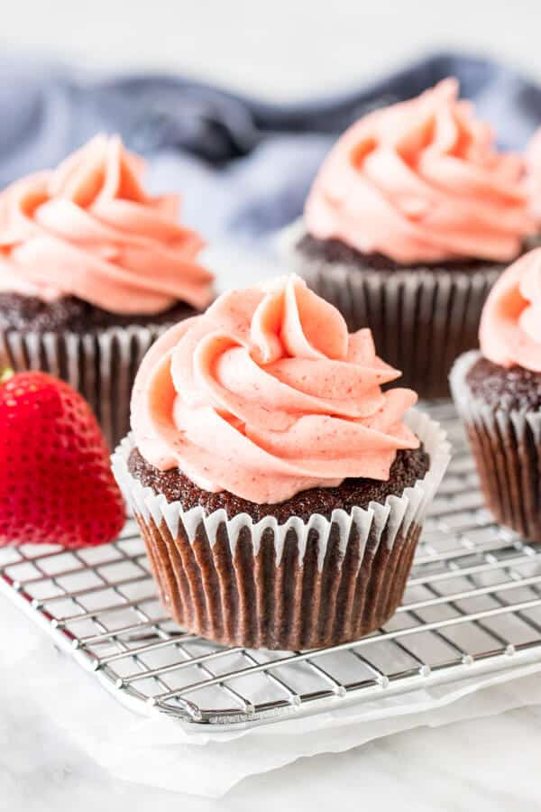 Chocolate cupcakes with strawberry frosting on cooling rack.