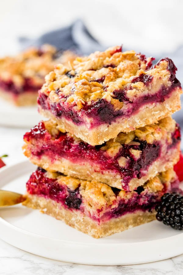 3 berry crumble bars made with oatmeal and brown sugar stacked on a white plate.