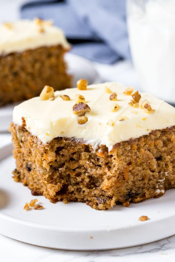 A slice of moist, tender carrot cake with a bite taken out of it on a white plate.