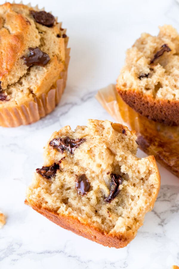 A moist peanut butter muffin with chocolate chips broken in half.