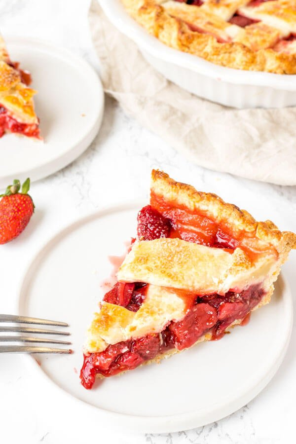 A slice of baked strawberry pie with lattice crust on top and a juicy berry pie filling.
