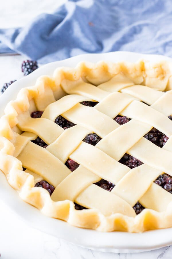Unbaked blackberry pie with a lattice crust and crimped edges.