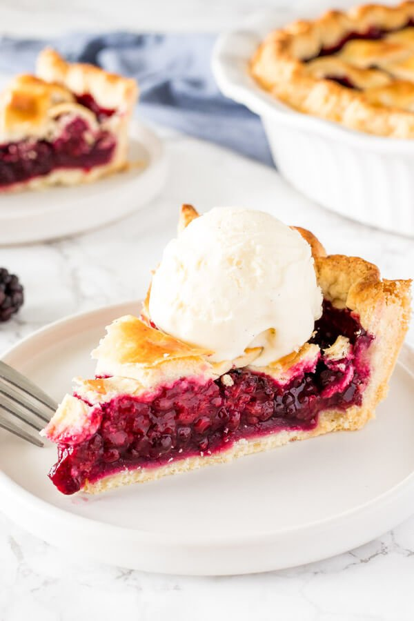 A slice of blackberry pie with flaky pastry and a scoop of vanilla ice cream on top.