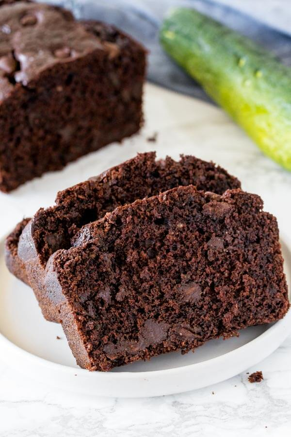 Slices of chocolate zucchini bread on a white plate.