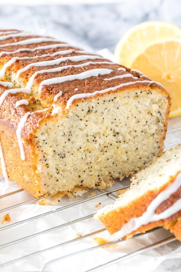 Lemon poppy seed bread on a cooling rack with a few slices cut to show the moist, tender texture of the bread.