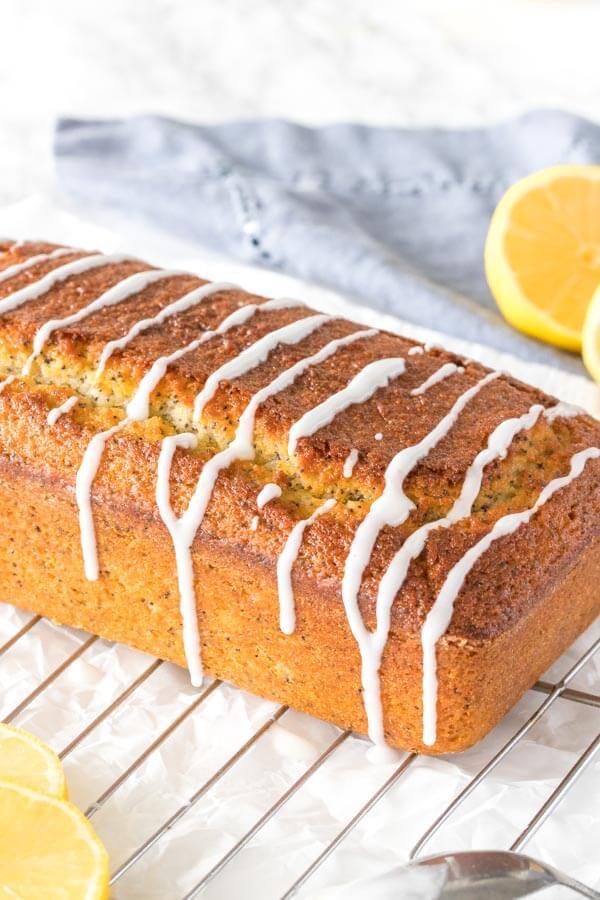 A loaf of lemon poppy seed bread with lemon glaze on a cooling rack.