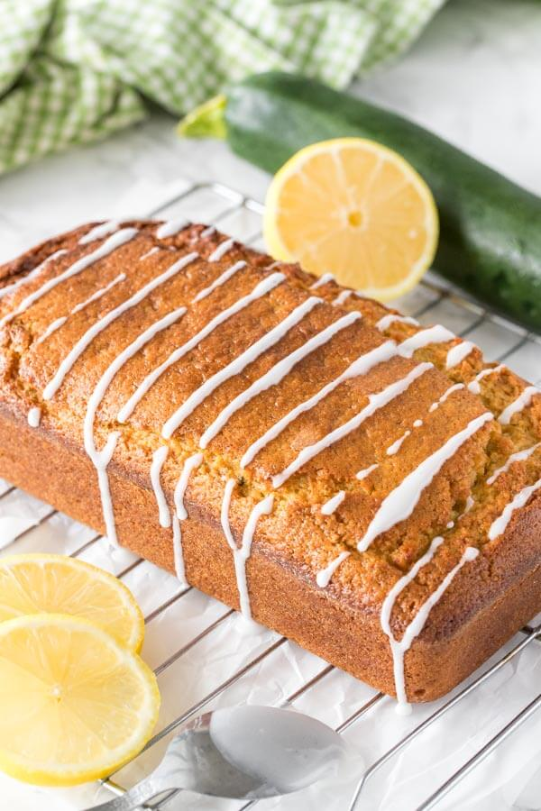 Fresh out of the oven lemon zucchini bread with a drizzle of lemon glaze on a cooling rack