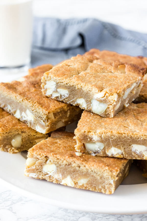 A plate of fudgy white chocolate macadamia nut blondies with a glass of milk in the background.