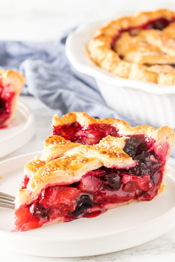 A slice of mixed berry pie with strawberries, blueberries and raspberries in the filling with a flaky lattice top crust.