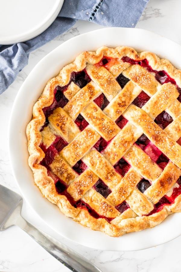 Mixed berry pie with a golden brown lattice crust and crimped edges fresh from the oven.