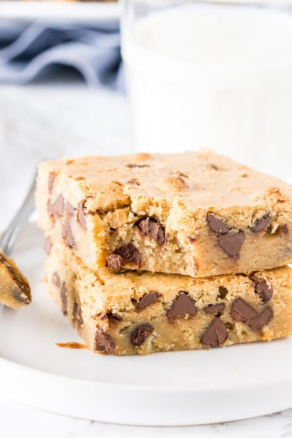 A stack of 2 chocolate chip blondies with a bite taken out of 1 to show the chewy, fudgy texture.