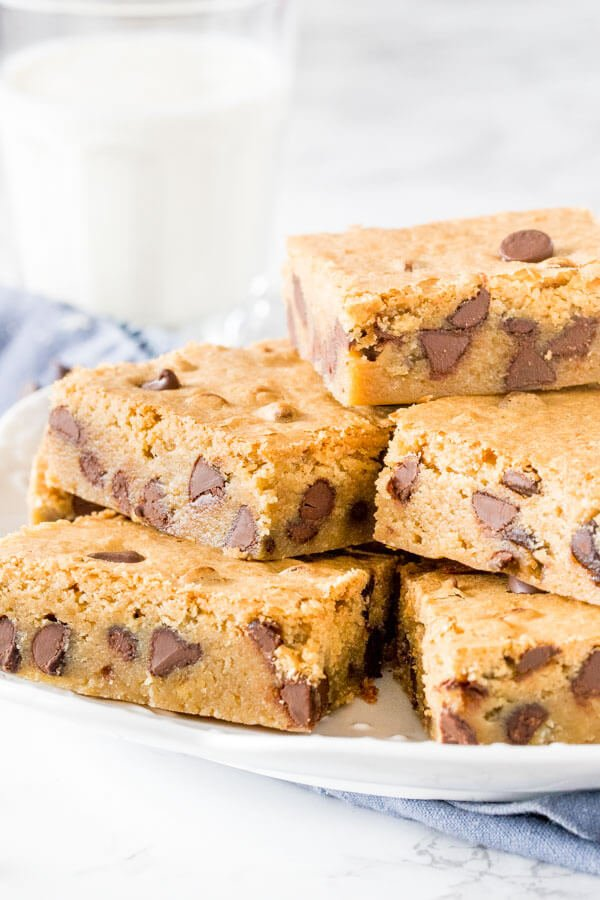 Chewy chocolate chip blondies cut into squares and stacked on a white plate with a glass of milk in the background.