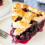 A slice of homemade blueberry pie with a juicy fruit filling and flaky lattice crust on top.