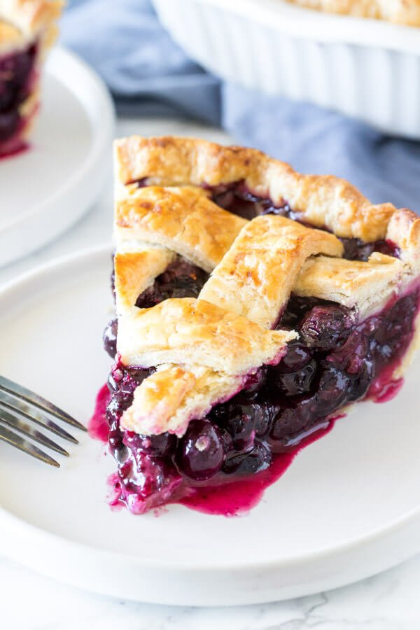 A slice of blueberry pie made with buttery, flaky homemade pie crust recipe