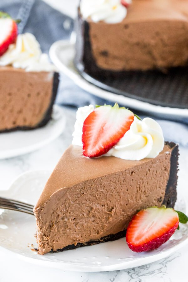 A slice of creamy, no-bake chocolate cheesecake with an oreo crust and topped with whipped cream and a strawberry on a white plate. A second slice of cheesecake and the whole cheesecake in the background.
