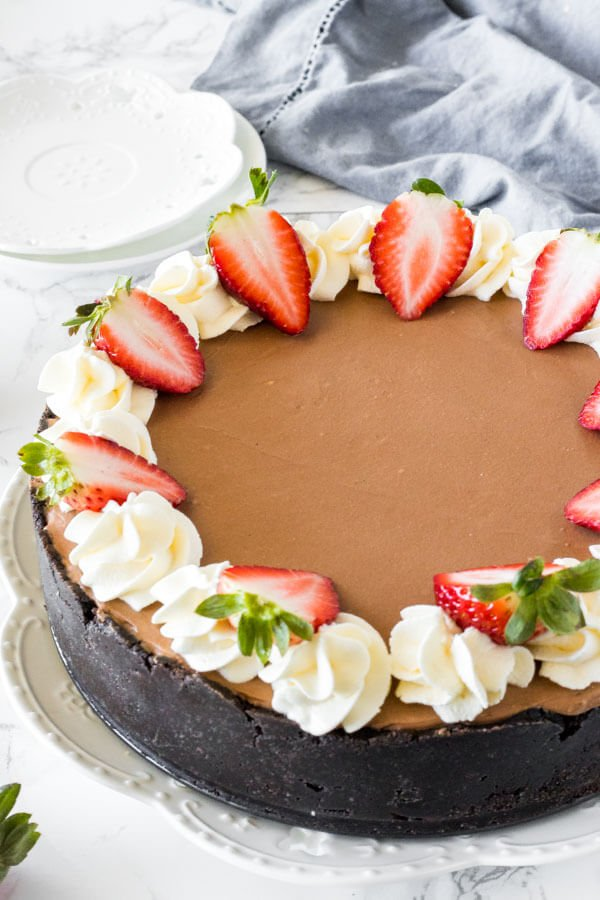 A full no bake chocolate cheesecake with an Oreo cookie crust that goes up the sides and decorated with whipped cream and strawberries around the edges.