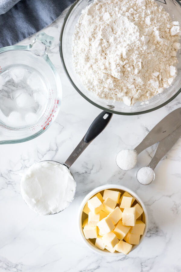 Overhead shot of ingredients for making this pie crust recipe: cubed butter, shortening, flour, salt, sugar and ice water.