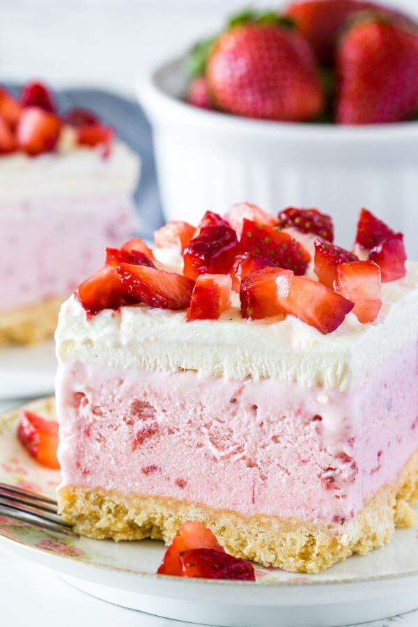 A slice of strawberry shortcake ice cream cake photographed from the side to show the cookie crust, thick layer of strawberry ice cream, layer of whipped cream and fresh cut strawberries on top.