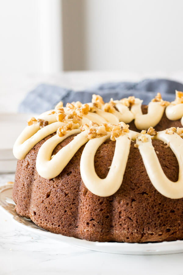 Moist banana bundt cake with a drizzle of thick cream cheese icing on top and sprinkled with walnuts.