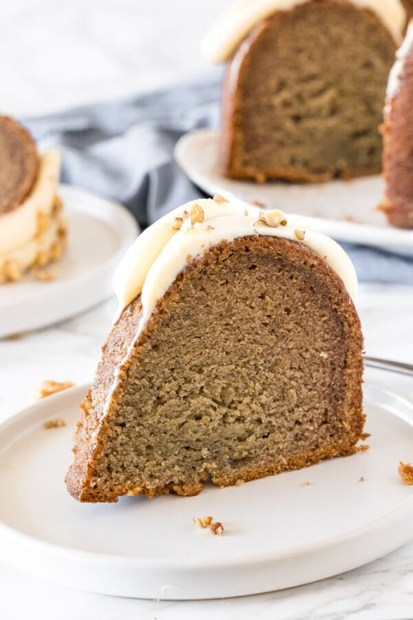 A slice of banana bundt cake with cream cheese frosting on a white plate.