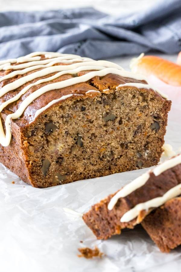 Banana carrot bread after slices have been cut to show the moist, tender crumb, grated carrots and walnuts.