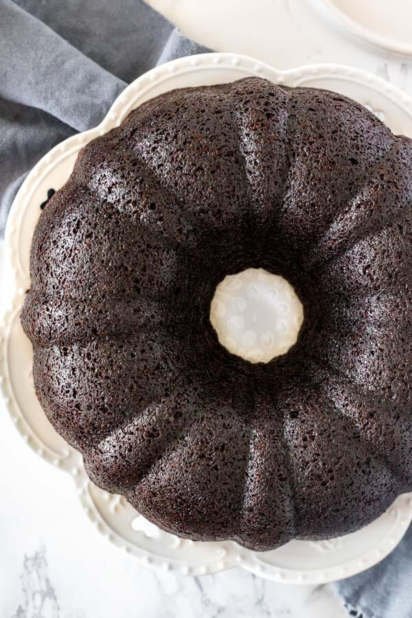 Baked chocolate bundt cake on a white plate after being inverted and getting out of the pan.