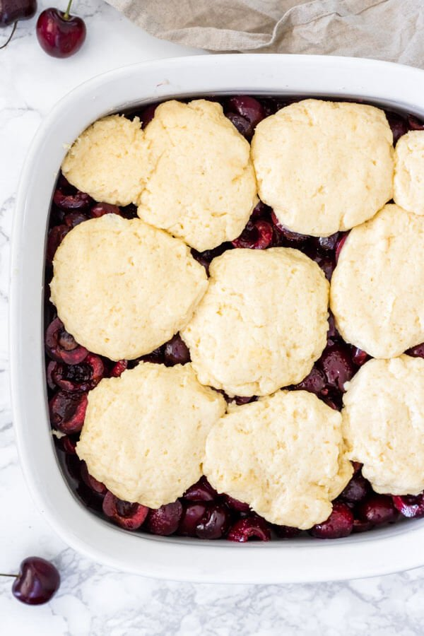 Cherry cobbler before going into the oven to be baked. The biscuit topping is cobbled on top of the fresh cherry layer.