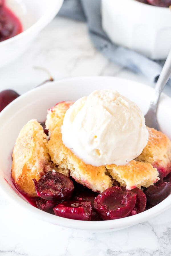 A bowl of fresh cherry cobbler with a flaky biscuit topping and scoop of vanilla ice cream on top.