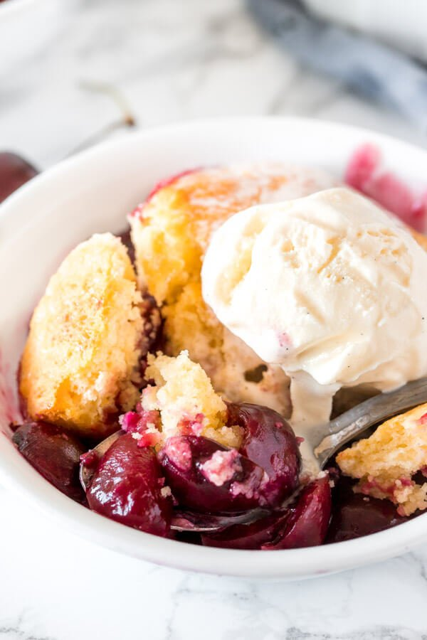Close up of a bite of cherry cobbler with sweet, juicy berries and buttery biscuit topping.