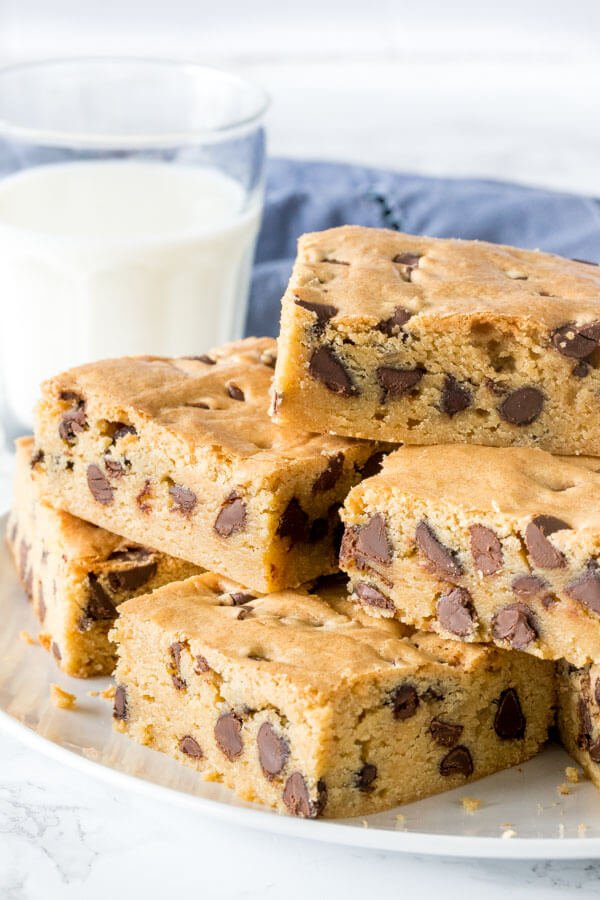 A plate of chocolate chip cookie bars stacked on top of each other to show their thick, chewy texture.