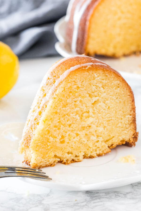 A slice of moist lemon bundt cake with a drizzle of lemon glaze on a white plate.