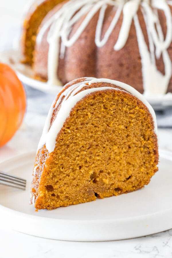 A slice of moist pumpkin bundt cake with cream cheese glaze on a white plate with the rest of the bundt cake in the background.
